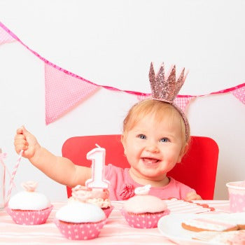 1 year old baby girl with pink birthday decorations