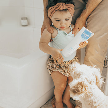 father and baby standing near bathtub with puppy