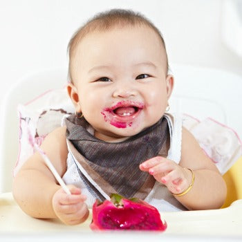 happy baby eating pink food in high chair