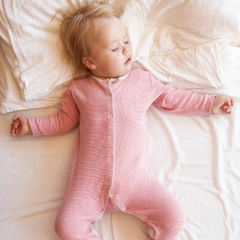 baby in pink pajamas sleeping on her back