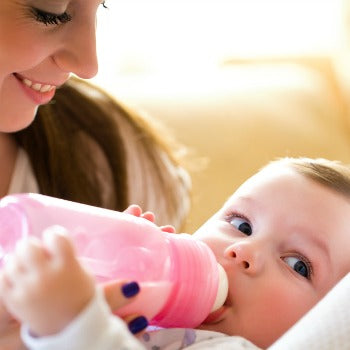 mother smiling at baby as she drinks from pink bottle