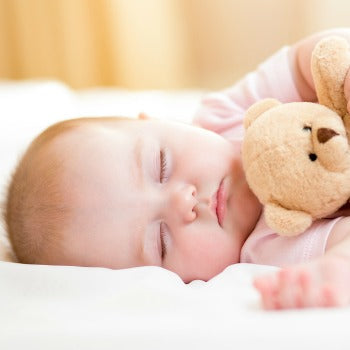 baby sleeping on her side while holding teddy bear
