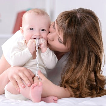 mother cuddling baby and kissing cheek as baby holds a pacifier