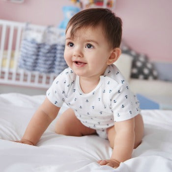 7 month old baby in onesie sitting on hands and knees on a bed