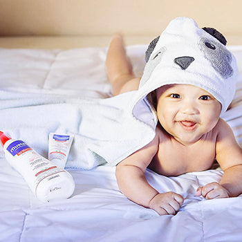 baby lying on tummy in hooded towel next to Mustela products