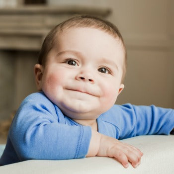 grinning baby leaning against a piece of furniture