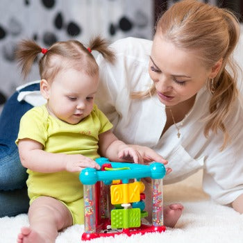 mother and baby girl playing with toy on white rug