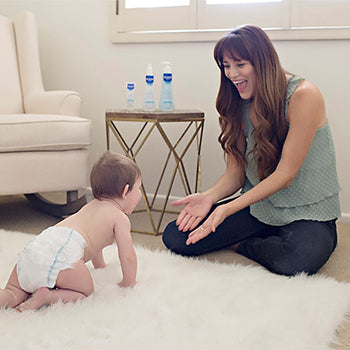 baby crawling towards mother on white rug