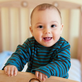 smiling baby in striped shirt leaning against table