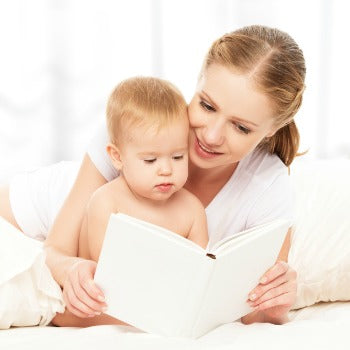 mother sitting behind baby while reading a book