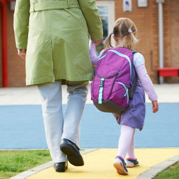 Father walking with his daughter at back to school time