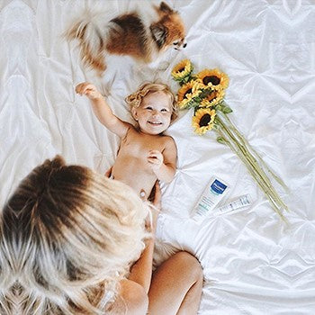 Happy Baby lying on a bed next to sunflowers