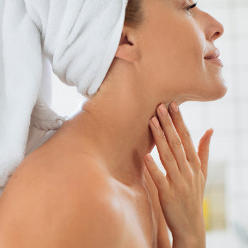 woman applying cream to her neck after taking a shower