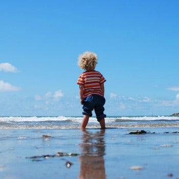 child standing in shallow beach water