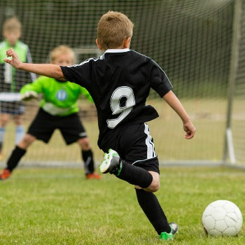 young boy playing soccer which is one of the many activities for children with eczema