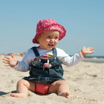 baby girl playing on a beach in sun hat