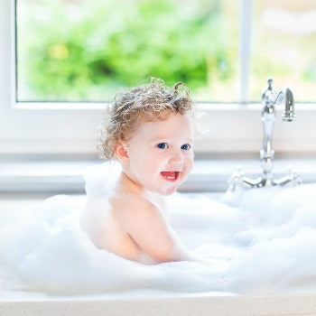 baby in bath with avocado oil for skin added to the water