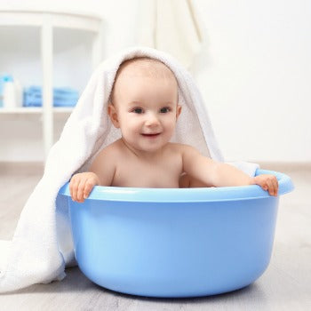 smiling baby in bathtub with towel draped over head