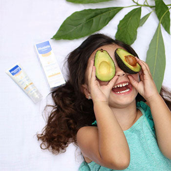 young girl holding avocado halves over eyes and giggling