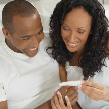 partners smiling together while looking at the results of a home pregnancy test