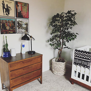 crib and dresser in the corner of a rustic baby nursery