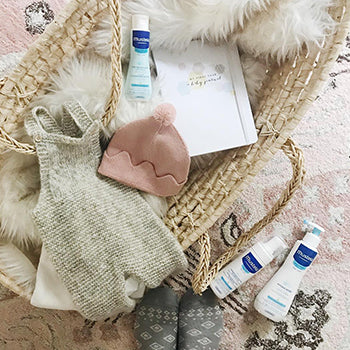 basket of newborn baby gift items and Mustela products