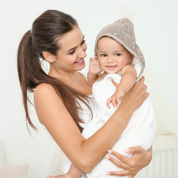 mother holding baby after a regular bath which can help treat baby dry scalp