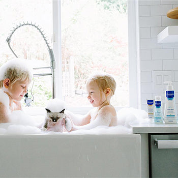 two small children bathing in kitchen sink with a kitten and Mustela bath products