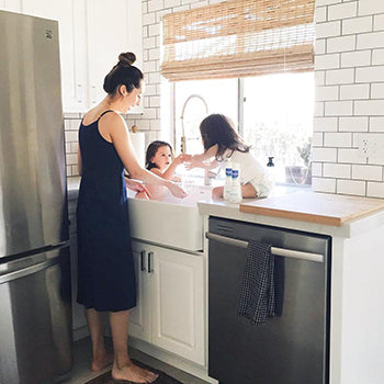 mother and girl bathing baby in sink