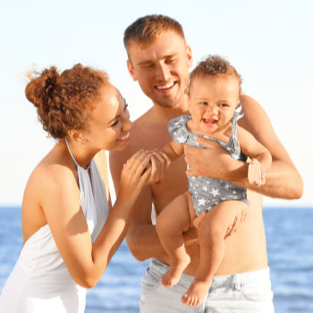 mom, dad, and baby in swimsuits at the beach