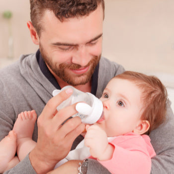 dad feeding baby a bottle, one of the baby essentials
