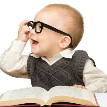 baby with glasses holding a book and already working on baby first words