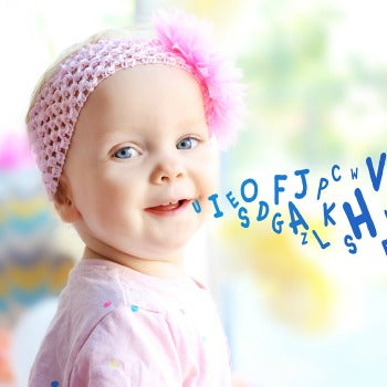 baby girl in pink headband with simulated baby first words coming out of her mouth