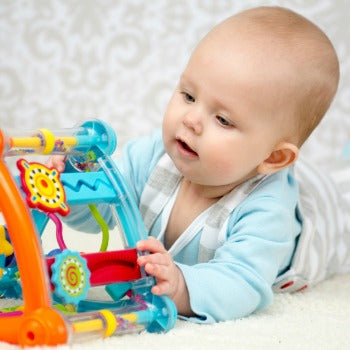 baby enjoying tummy time with a colorful interactive toy