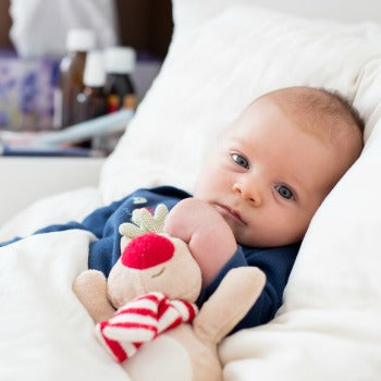 baby relaxing in bed with a toy