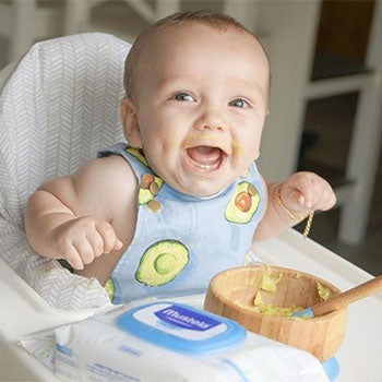 happy baby eating mashed avocado in a high chair with Mustela's cleansing wipes nearby