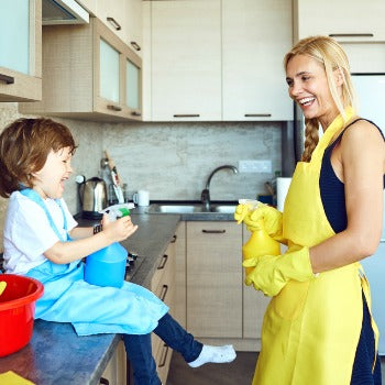 mother and young boy playing with squirt bottles in a kitchen