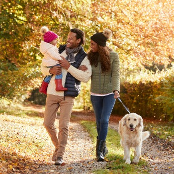 small family walking outdoors with their pet