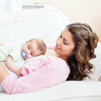 baby lying on mother's tummy while in bed