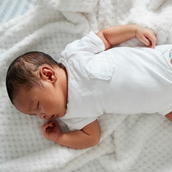 baby in white lying on back with head turned to the side