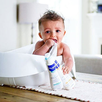 infant sitting in bath holding wash cloth and bath products