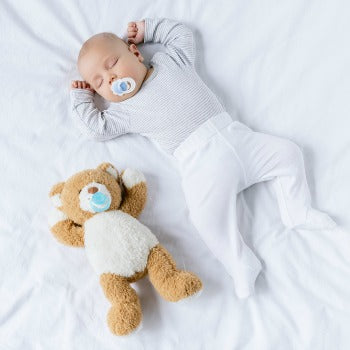 baby with pacifier in mouth sleeping next to a teddy bear
