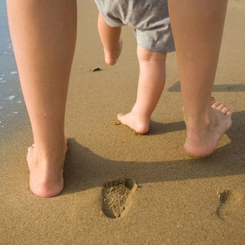 mother and baby walking in the sand