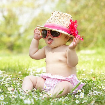 baby playing in the shade with protective sunglasses and hat