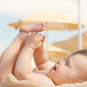 baby playing on a towel at the beach