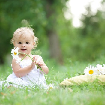 baby playing with flower in grass