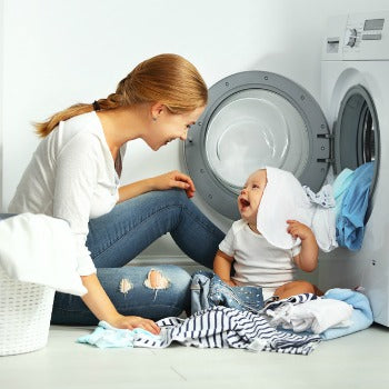 mom and baby in front of washing machine doing cloth diaper laundry