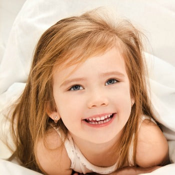 young girl smiling and looking upwards from under blankets