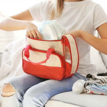 mother packing diapers and other diaper bag essentials