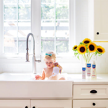 baby girl playing in sink of water next to fragrance-free bath products